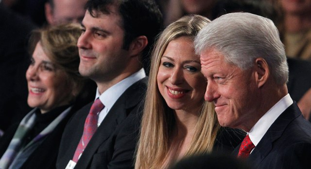 Chelsea Clinton smiles as she looks at her father, former U.S. President Bill Clinton, during the final day of the Clinton Global Initiative 2012 in New York